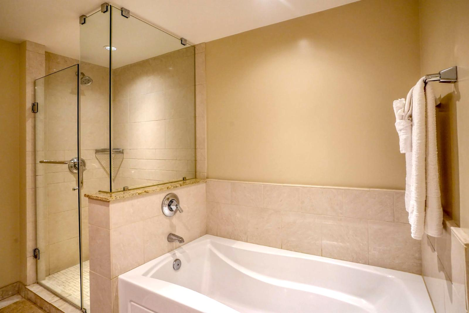 Floor to ceiling glass enclosed shower and tub combination, perfect for relaxing