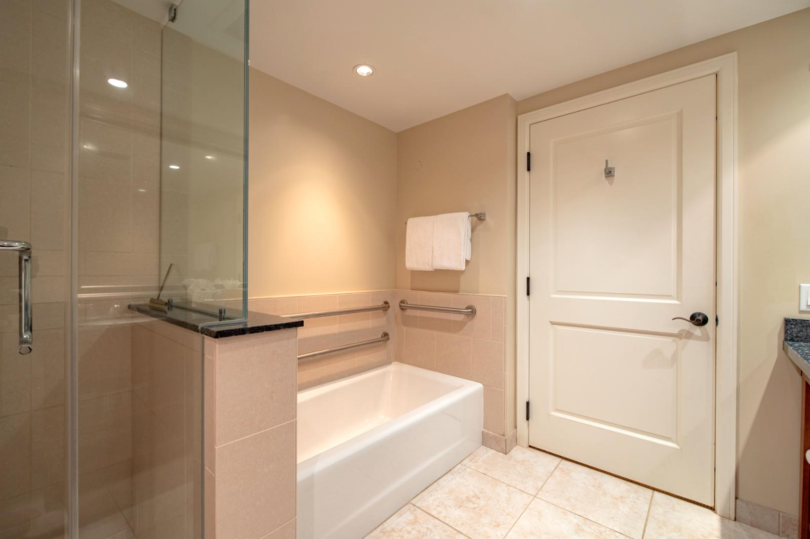 Floor to ceiling glass enclosed shower with adjacent tub