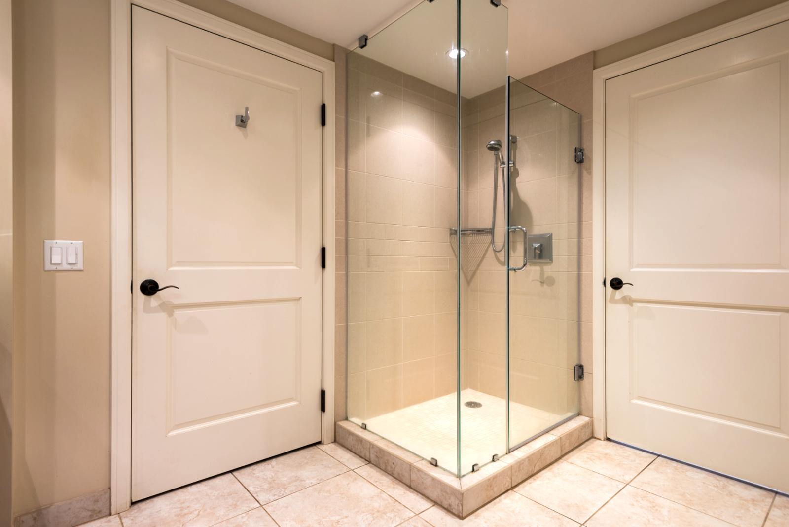 Floor to ceiling glass enclosed shower fine tile details