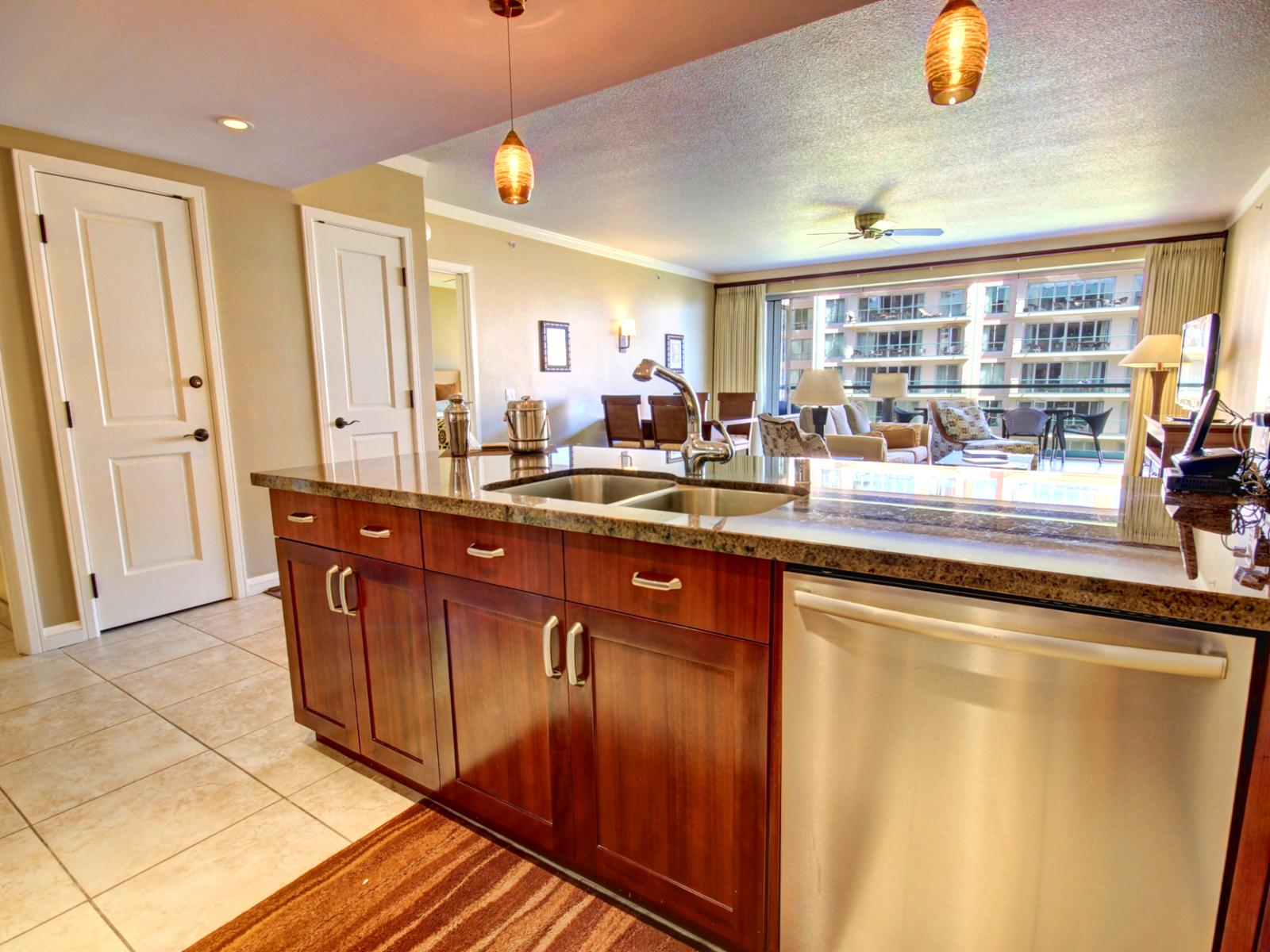 Looking out from this gourmet kitchen into the expansive living room that opens up to a spacious lanai.