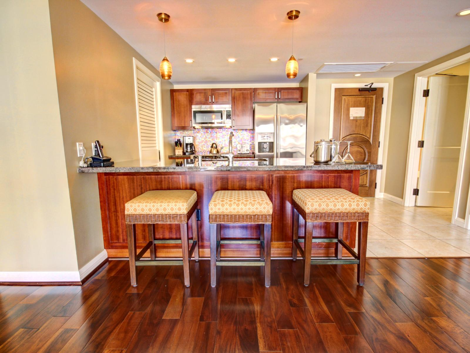 Gourmet kitchen, with bar stools and entrance to the unit.