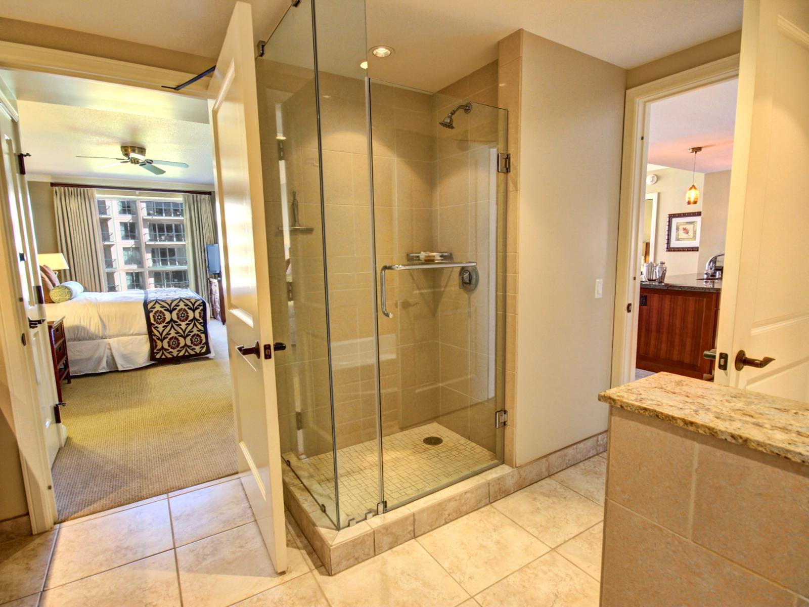 Separate glassed in shower showing both access to living room and bedroom.