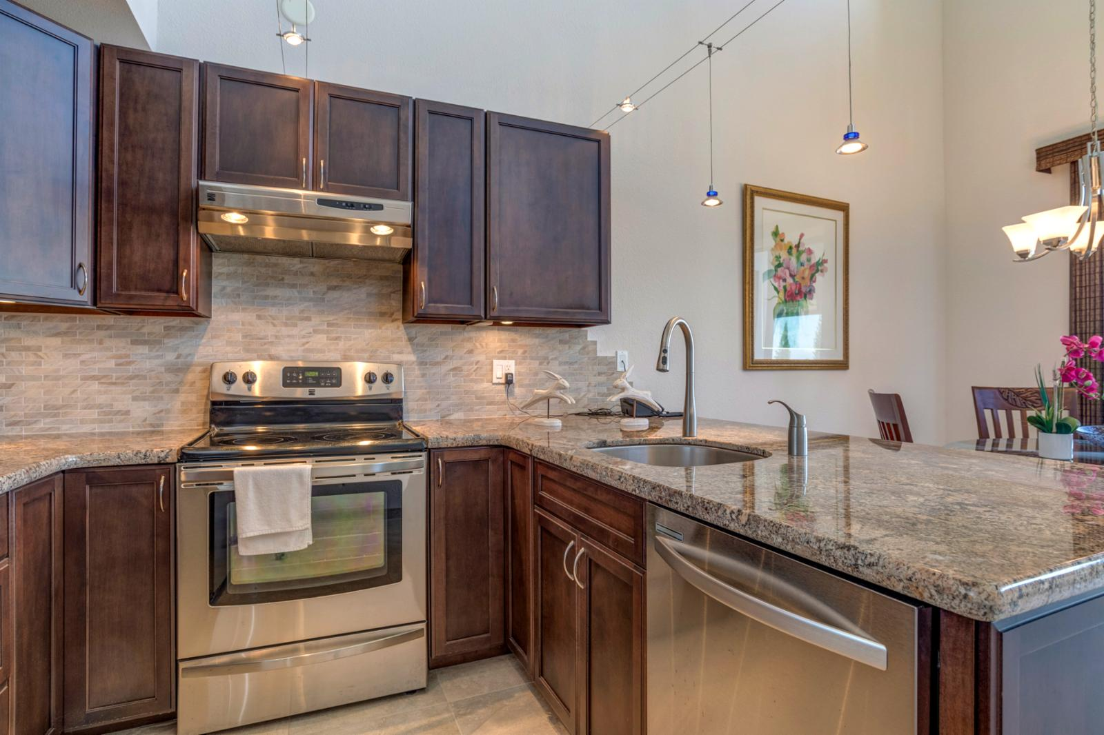 Stainless steel appliances throughout, vaulted ceilings above kitchen