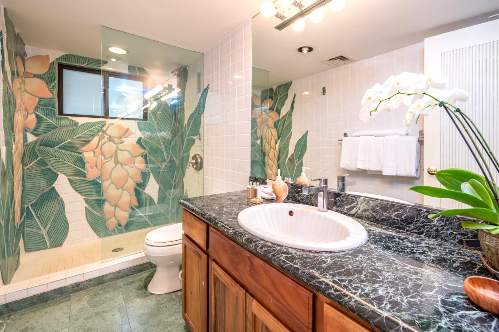 Custom tile work and floor to ceiling glass enclosed shower