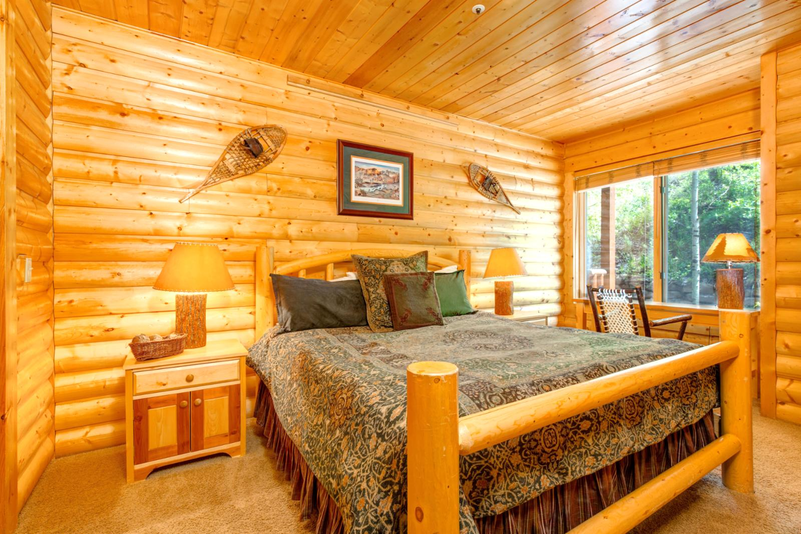 A quiet king size bed located in the back of the condo with views of trees and mountainside